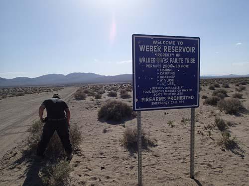 Här äger urinvånarna marken, observera den sönderskjutna skylten som anger förbud mot vapen....