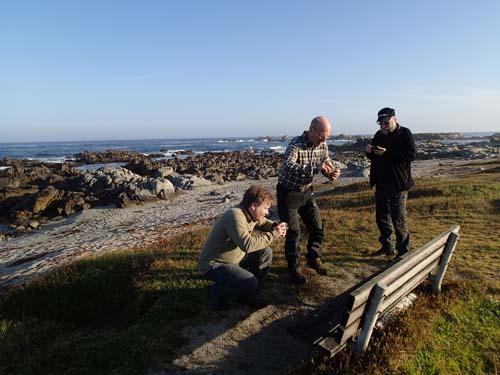 Tre män vid en bänk med utsikt, ingen bryr sig om havet, alla tittar på bänken - är det inte typiskt för burkjägare?