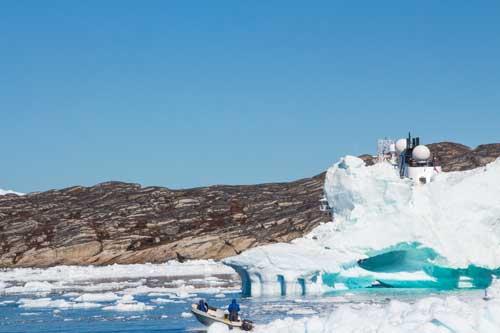 Två säljägare i en båt, med gevär på ryggen. Bakom isberget skymtar MS Fram.
