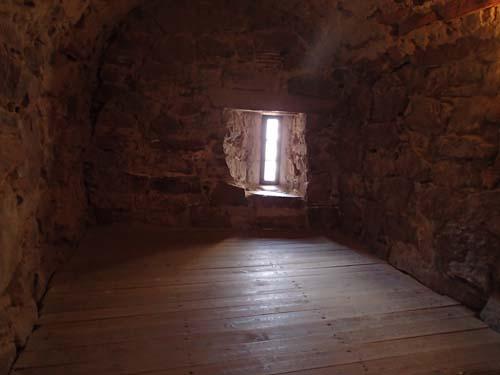 Det var inte mycket ljus i det lilla rummet ovan fängelset, endast lite ljus genom en skottglugg.