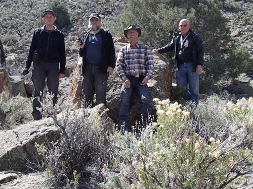 Fyra gubbar vid en stor sten.